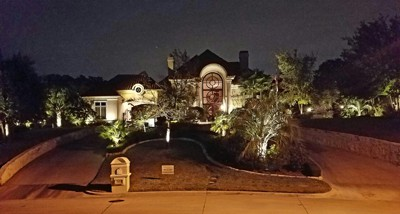 Street view of a home at night lit up by exterior LED lighting