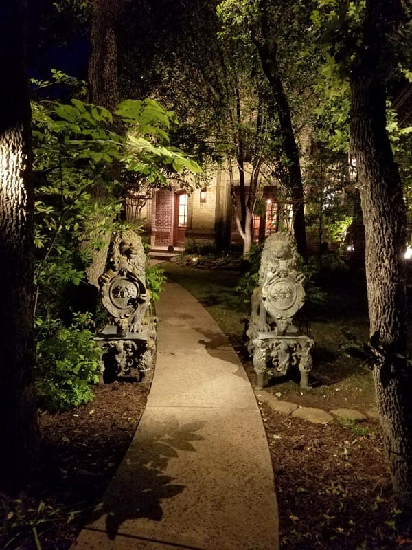 A garden path illuminated at night by landscape lighting