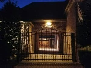 Wrought iron fence in front of well lit home
