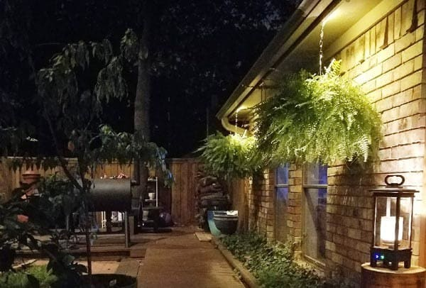 A patio with a grill and lighting for the path and to highlight hanging plants and brick of house