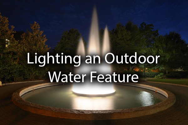 A gorgeous fountain with the words, lighting an outdoor water feature.